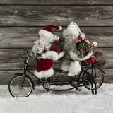 Two funny santa claus on a tandem in hurry for christmas shoppin. G. Witty advent decoration for december Stock Photo