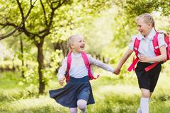 Two funny school girls with school backpacks running holding hands outdoor. S Stock Images