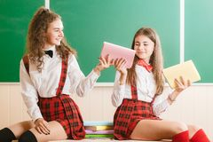 Two funny schoolgirls in school uniforms are sitting on the background of a green board on the desk with books