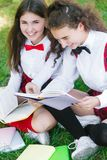 Two funny schoolgirls sit on the grass and read books. Girls, girlfriends, sisters are taught lessons in nature stock photography