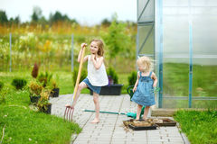 Two funny sisters with garden tools Royalty Free Stock Photo