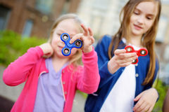 Two funny sisters playing with fidget spinners on the playground. Popular stress-relieving toy for school kids and adults. Royalty Free Stock Photo