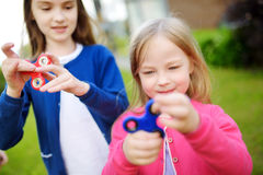 Two funny sisters playing with fidget spinners on the playground. Popular stress-relieving toy for school kids and adults. Royalty Free Stock Images