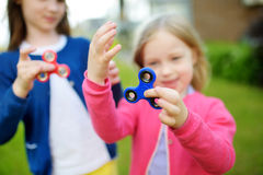 Two funny sisters playing with fidget spinners on the playground. Popular stress-relieving toy for school kids and adults. Royalty Free Stock Image