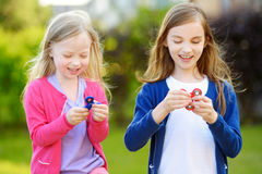 Two funny sisters playing with fidget spinners on the playground. Popular stress-relieving toy for school kids and adults. Stock Photography