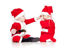 Two funny small kids in Santa Claus clothes Stock Photo