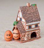 Two funny smiling eggs near a house Stock Photo