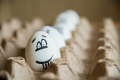Two funny smiling eggs in a packet. Easter eggs with fun painted faces in a packet Stock Image