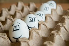 Two funny smiling eggs in a packet. Easter eggs with fun painted faces in a packet Royalty Free Stock Photo