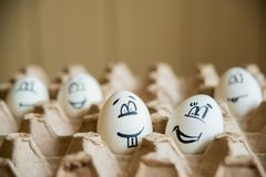 Two funny smiling eggs in a packet. Stock Photos