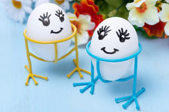 Two funny smiling eggs on stands and flowers, selective focus Stock Photo