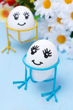 Two funny smiling eggs on stands and flowers Royalty Free Stock Image