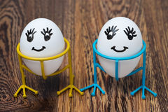 Two funny smiling eggs on stands on a wooden background Stock Photography