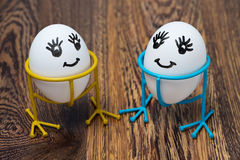Two funny smiling eggs on stands, on a wooden table Stock Photography