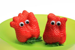 Two funny strawberries with jiggle eyes. Two funny fresh strawberries with jiggle eyes Royalty Free Stock Photography