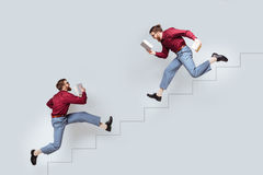 Two funny twin men with books running up and down Royalty Free Stock Images