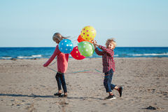 Two funny white Caucasian children kids with colorful bunch of balloons, playing running on beach on sunset, autumn summer stock photo
