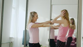 Two funny women dancing in the bedroom dance. Pajama party girlfriends. Two fun teen woman dancing in the bedroom. Repeat the dance movements, looking at mobile stock video footage