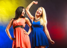Two funny women in dresses. Party, celabration, carnival. Two attractive funny dancing women in dresses on colorful background stock photos
