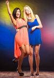 Two funny women in dresses. Party, celabration, carnival. Two attractive funny dancing women in dresses on colorful background in studio stock image