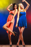 Two funny women in dresses. Party, celabration, carnival. Two attractive funny dancing women in dresses on colorful background in studio royalty free stock photography
