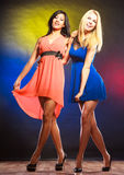 Two funny women in dresses. Party, celabration, carnival. Two attractive funny dancing women in dresses on colorful background in studio royalty free stock photos