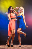 Two funny women in dresses. Party, celabration, carnival. Two attractive funny dancing women in dresses on colorful background in studio stock images