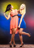 Two funny women in dresses. Party, celabration, carnival. Two attractive funny dancing women in dresses on colorful background in studio stock photo
