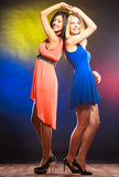 Two funny women in dresses. Party, celabration, carnival. Two attractive funny dancing women in dresses on colorful background in studio stock photos
