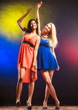 Two funny women in dresses. Party, celabration, carnival. Two attractive funny dancing women in dresses on colorful background in studio stock photography