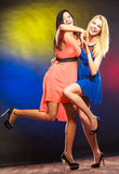 Two funny women in dresses. Party, celabration, carnival. Two attractive dancing women with funny hands gesture in dresses on colorful background in studio stock image