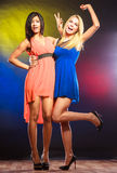 Two funny women in dresses. Party, celabration, carnival. Two attractive dancing women with funny hands gesture in dresses on colorful background in studio stock images