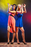 Two funny women in dresses. Party, celabration, carnival. Two attractive dancing women with funny hands gesture in dresses on colorful background in studio royalty free stock photography