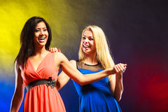 Two funny women holding hands in dresses. Royalty Free Stock Photography