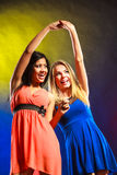Two funny women holding hands in dresses. Royalty Free Stock Image