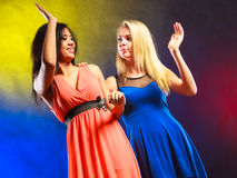 Two funny women making hands high five in dresses. Royalty Free Stock Images