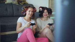 Two funny women play console games with gamepad and have fun at home. Two funny women play console computer games with gamepad and have fun at home stock video footage