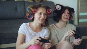 Two funny women play console games with gamepad and have fun at home stock video