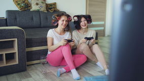 Two funny women play console games with gamepad and have fun at home stock video footage