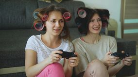 Two funny women play console games with gamepad and have fun at home. Two funny women play console computer games with gamepad and have fun at home Stock Image