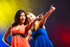 Two funny women showing something in dresses. Party, celabration, carnival. Two attractive funny dancing women showing something in dresses on colorful royalty free stock image