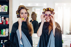 Two funny young girlfriends in hair curlers wearing capes having fun time together in beauty salon. Female friends Royalty Free Stock Photos