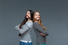 Two funny young women making moustache with their hair Stock Images