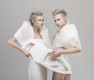 Two futuristic blonde women in white outfit Royalty Free Stock Photo