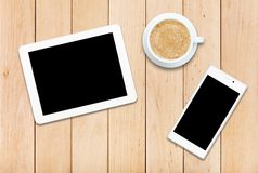 Two gadgets and coffee on a wooden table Stock Photography