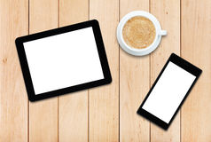 Two gadgets and coffee on a wooden table Stock Image