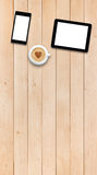 Two gadgets and coffee on a wooden table Royalty Free Stock Photo