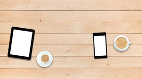Two gadgets and coffee on a wooden table Stock Photo