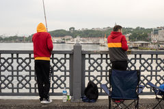 Two Galatasaray S.K. Fans Fishing on Galata Bridge in Early Morn Royalty Free Stock Image