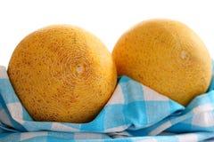 Two galia melon on white-blue checkered kitchen towel Stock Photography